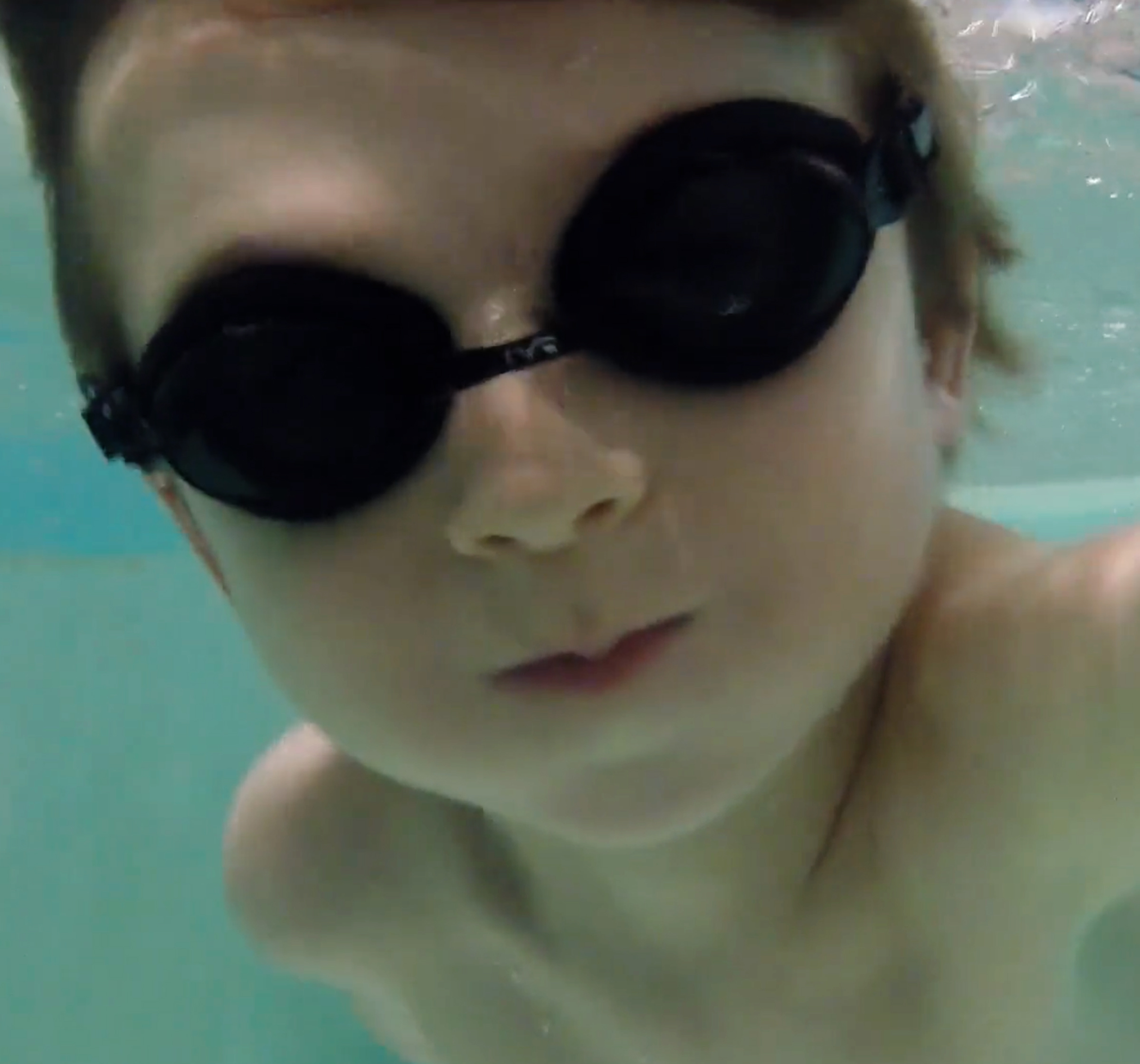 Boy with goggles underwater looking at the camera