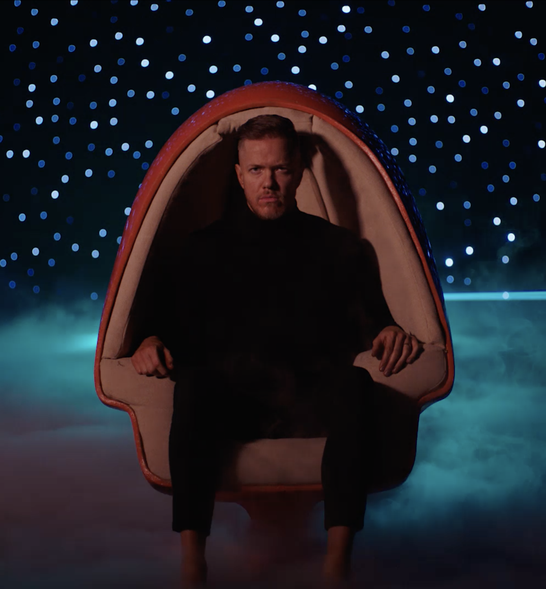 Dan Reynolds sitting in retro chair floating over earth.