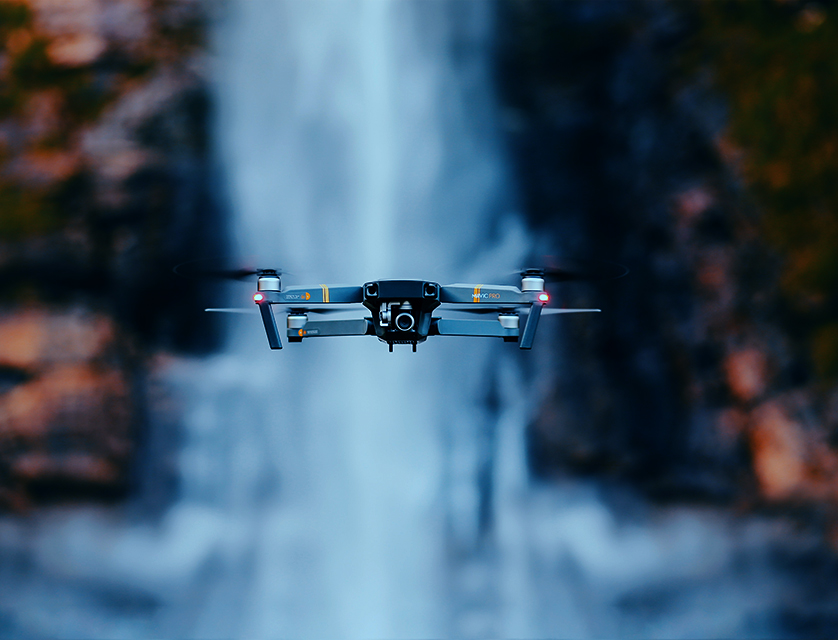 Hovering drone in front of waterfall